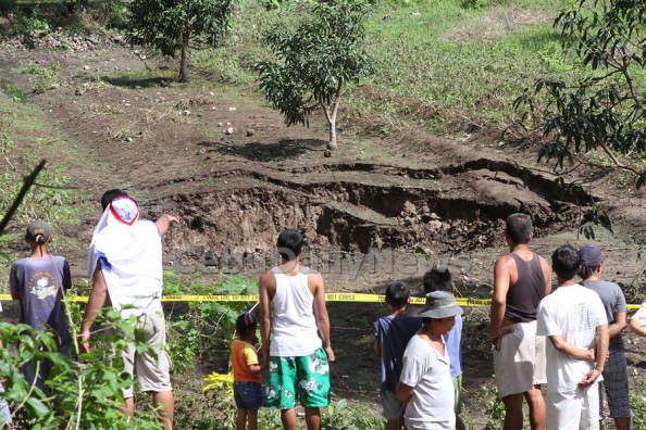 Curious onlookers gather outside a yellow police cordon at the site of the nrew sinkhole in Dumnajug town, southwestern Cebu. (CDN PHOTO/ JUNJIE MENDOZA)