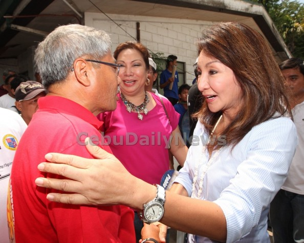 Former Consolacion mayor Avelino Gungob, Sr. (left) shares hands with Cebu Gov. Gwendolyn Garcia during a summit in the town. (JUNJIE MENDOZA)