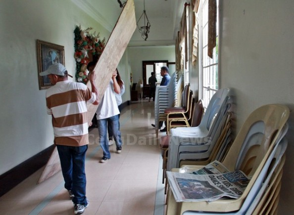 Capitol employees remove plywood shields from windows near the office of the suspended Gov. Gwen Garcia. (JUNJIE MENDOZA)
